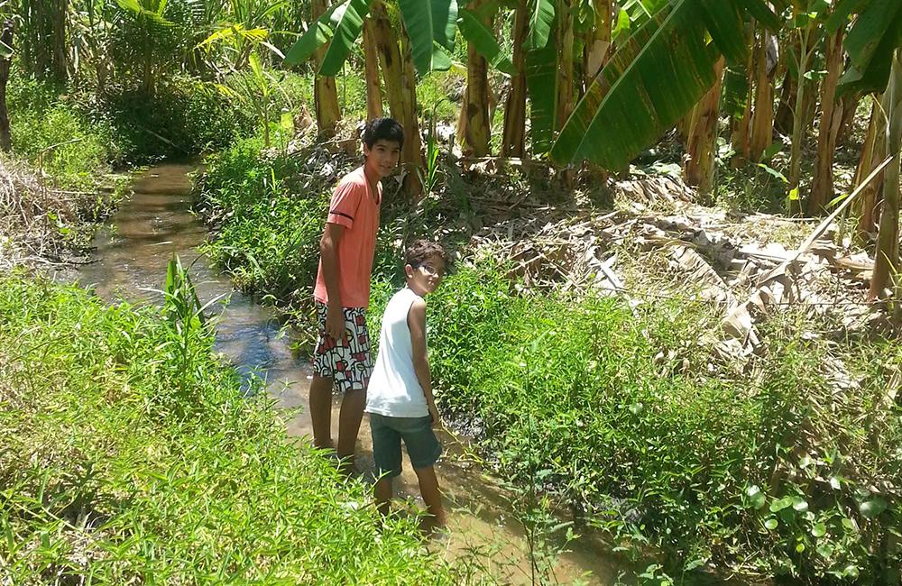 Zwei Kinder an einem kleinen Flußlauf auf der Nòs na Vida Farm.
